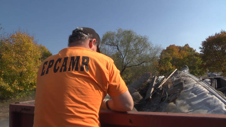 Bobby Hughes, director of EPCAMR, helps load trash and other junk found during Centralia's cleanup day.