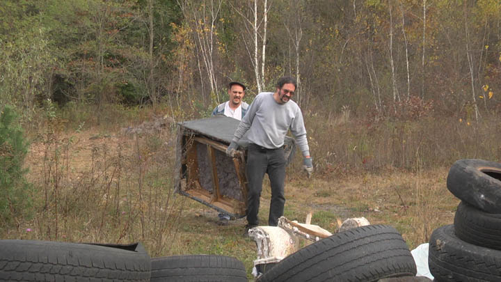 Two volunteers hauling a junk couch found in the woods around Centralia PA.