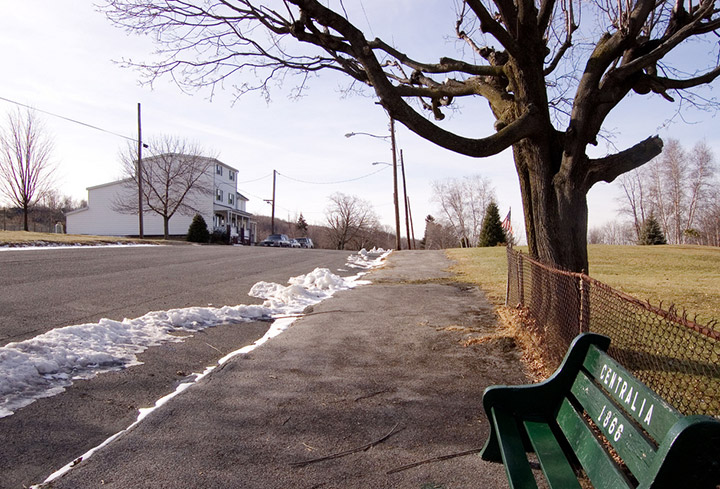 Green Centralia Pennsylvania bench with John Lokitis' home in the background. Credit: Flickr/mdesjardin